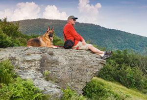 man hiking with dog
